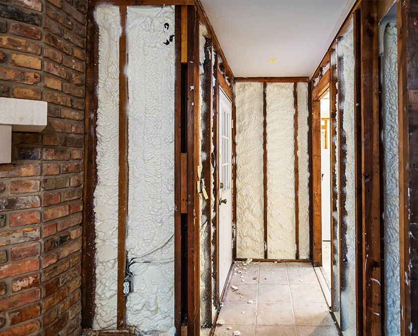 Spray foam insulation applied on interior brick walls.